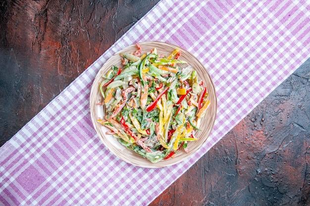 Vista superior da salada de vegetais no prato na toalha da mesa na mesa vermelha escura, lugar grátis