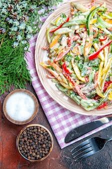 Vista superior da salada de vegetais no prato na toalha de mesa, garfo e faca, sal e pimenta preta ramos de pinheiro na mesa vermelha escura