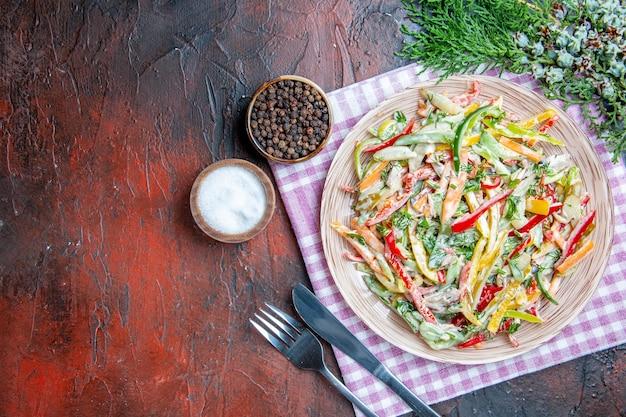 Vista superior da salada de vegetais no prato no garfo da toalha de mesa e na faca sal e pimenta do reino no espaço livre da mesa vermelha escura