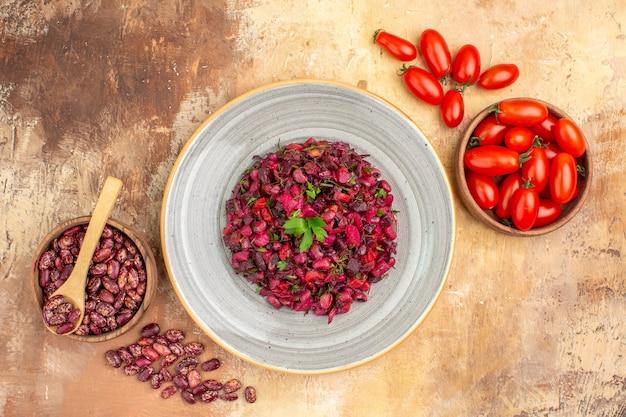 Vista superior da salada de vinagre com feijão dentro e fora da panela marrom com colher e tomates em fundo de cor mista