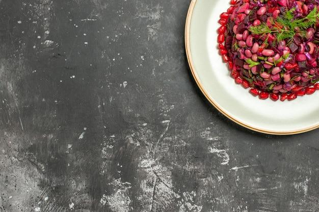 Vista superior da salada de vinagrete com romãs e feijão na superfície escura