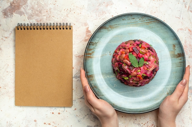 Vista superior da salada de vinagrete em prato oval em caderno de mão feminina em mesa cinza claro