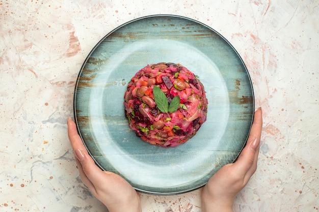 Vista superior da salada de vinagrete em prato oval na mão da mulher em mesa cinza claro