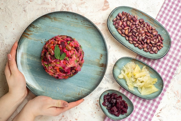Vista superior da salada de vinagrete em prato redondo na mão da mulher repolho em conserva feijão cortado beterraba em pratos na mesa cinza claro