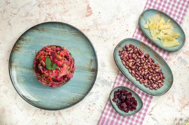 Vista superior da salada de vinagrete no prato repolho em conserva feijão cortado beterraba em pratos na mesa cinza claro