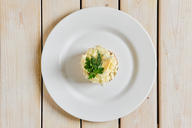 Vista superior da salada em camadas com arroz, cenoura, pepino em conserva, carne desfiada e queijo