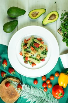 Vista superior da salada fresca com queijo parmesão nozes abacate tomate cereja e morangos em uma tigela branca