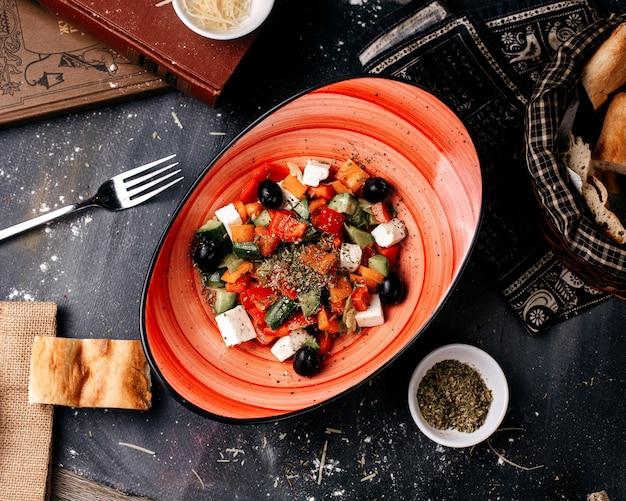 Vista superior da salada grega com vitamina fresca enriquecida com legumes fatiados dentro de chapa preta e junto com pão na superfície escura