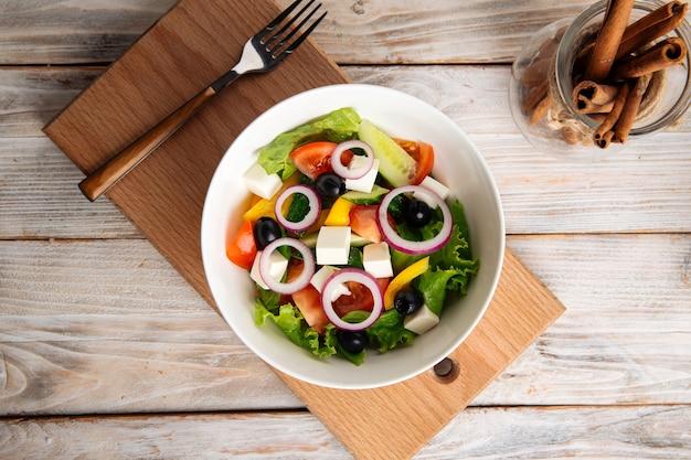 Vista superior da salada grega de legumes frescos em uma tigela branca na placa de madeira
