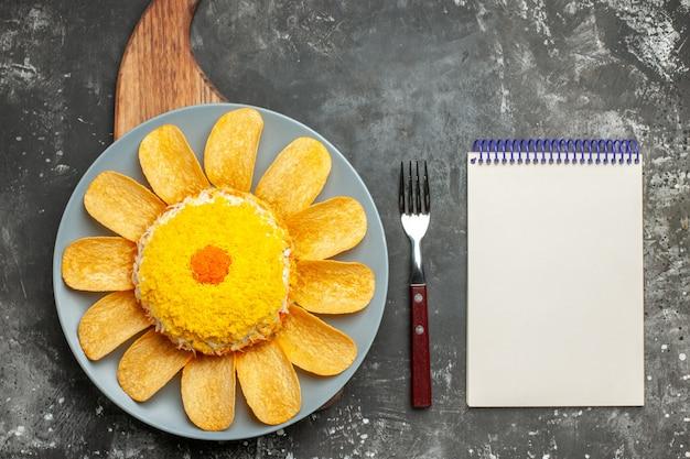 Vista superior da salada no centro com o suporte do prato embaixo dele e garfo e bloco de notas ao lado na mesa cinza escuro