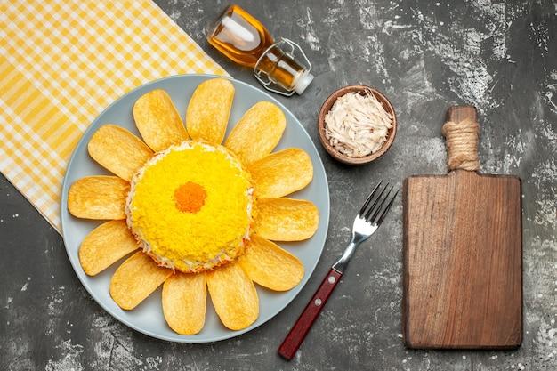 Vista superior da salada no lado esquerdo com guardanapo amarelo embaixo, com garrafa de óleo de garfo de queijo e tábua de cortar na mesa cinza escuro