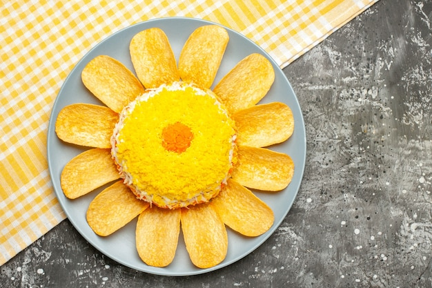 Vista superior da salada no lado esquerdo com guardanapo amarelo embaixo na mesa cinza escuro