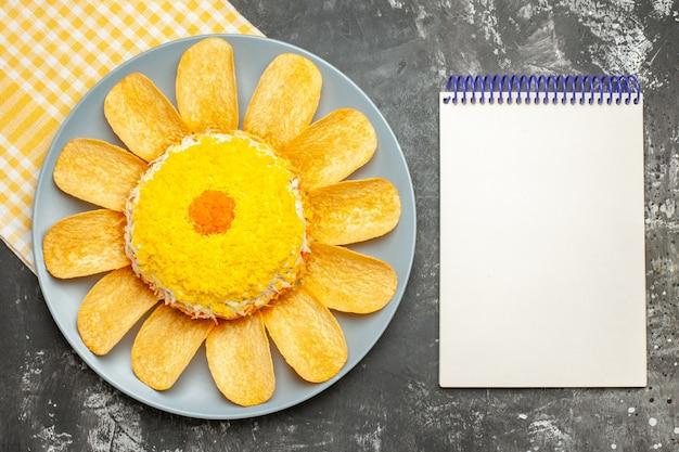 Vista superior da salada no lado esquerdo do meio com guardanapo amarelo embaixo e bloco de notas na lateral em fundo cinza escuro