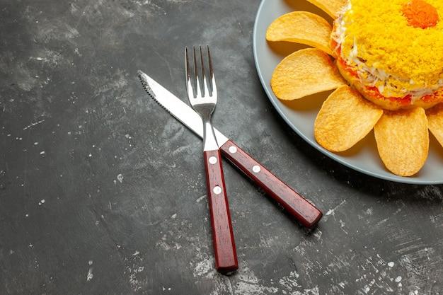 Vista superior da salada no lado superior direito com garfo e faca cruzados no lado em fundo escuro