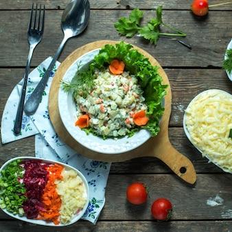 Vista superior da salada olivier russa tradicional com ervilha de frango verde e legumes em um prato branco em uma placa de madeira