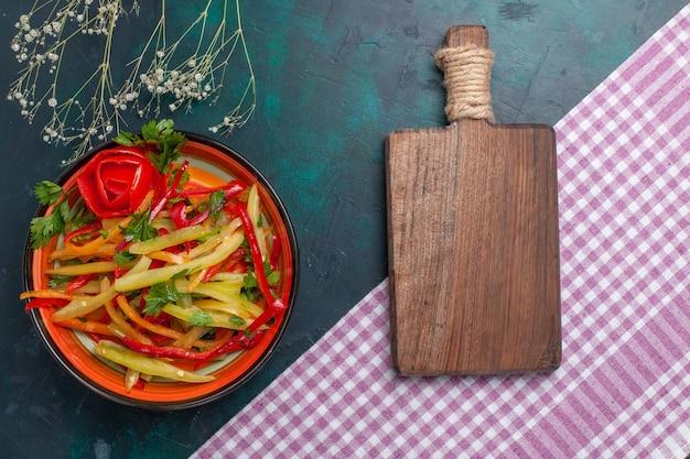 Vista superior da salada picante em fatias de pimentão colorido na mesa azul-escura