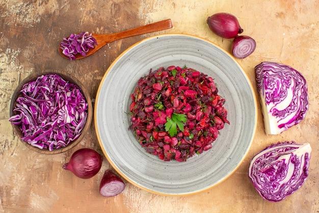 Vista superior da salada saudável à base de repolho roxo picado de cebola roxa e outros vegetais frescos em um grande prato de cerâmica sobre um fundo de madeira