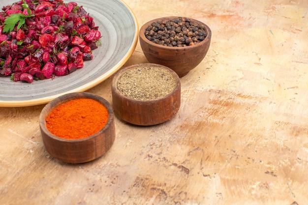 Vista superior da salada saudável em um prato cinza com pimenta preta moída açafrão-da-índia em um fundo de madeira com espaço livre para texto
