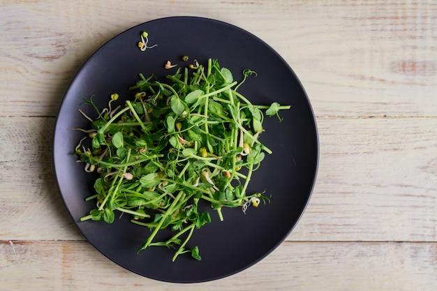 Vista superior da salada saudável vegana feita de brotos de ervilhas microgreen e feijão germinado na parede de madeira