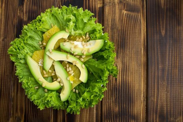 Vista superior da salada vegetariana com abacate, folhas de alface, laranja e pinhões