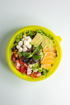 Vista superior da salada verde com alface tomate cereja abacate laranja milho e mussarela
