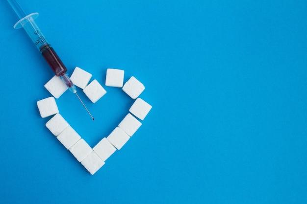Vista superior da seringa com sangue e açúcar no azul