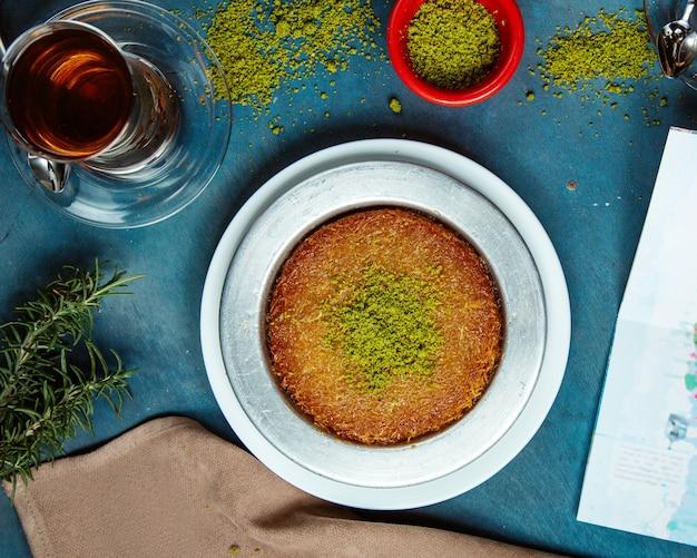 Vista superior da sobremesa kunefe, guarnecida com pistache, servida com chá preto