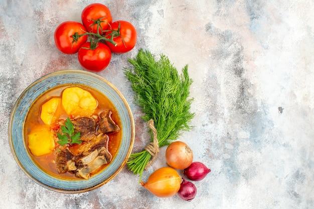 Vista superior da sopa bozbash caseira um punhado de tomates e cebolas de endro na superfície nua