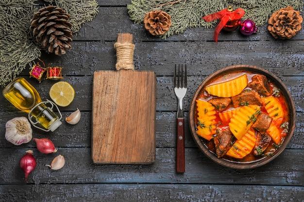 Vista superior da sopa carnuda com batatas e verduras na mesa azul-escura
