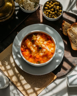 Vista superior da sopa com couve-flor cenoura e batatas em uma placa de madeira