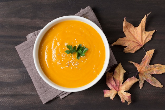 Vista superior da sopa creme e folhas de outono