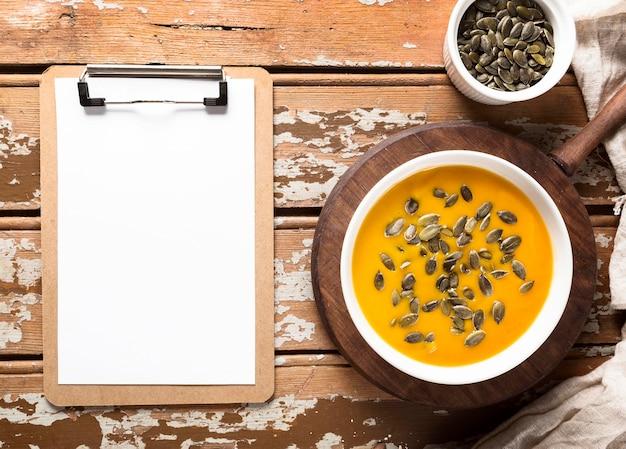 Vista superior da sopa de abóbora com sementes e bloco de notas