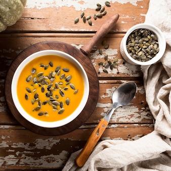 Vista superior da sopa de abóbora com sementes e colher
