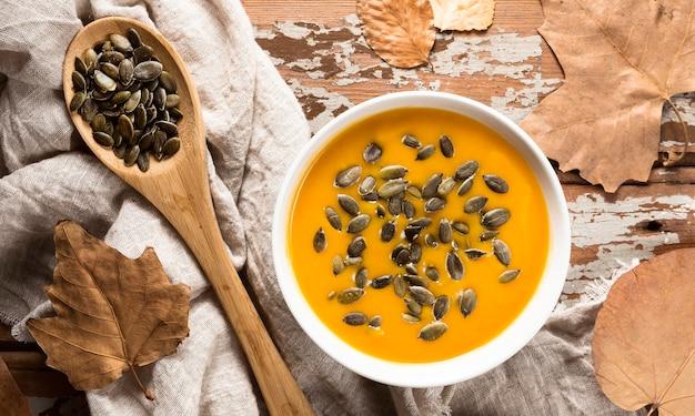 Vista superior da sopa de abóbora com sementes e folhas