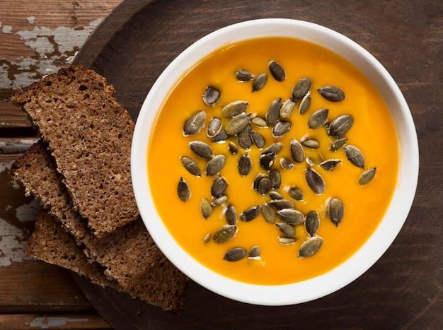 Vista superior da sopa de abóbora com sementes e pão