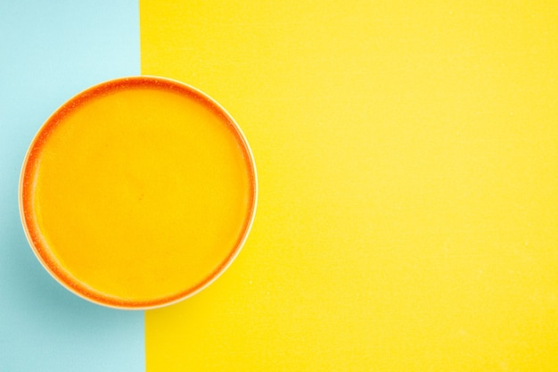 Vista superior da sopa de abóbora dentro do prato em fundo colorido