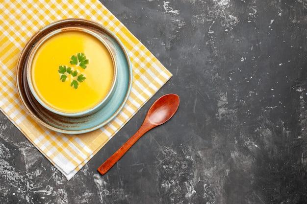 Vista superior da sopa de abóbora dentro do prato em fundo escuro