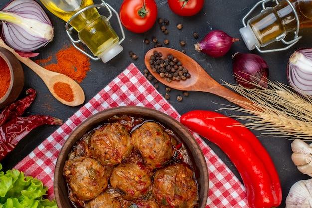 Vista superior da sopa de almôndega grande em uma tigela de pimenta vermelha em pó em uma garrafa de cebola pequena de alface na mesa