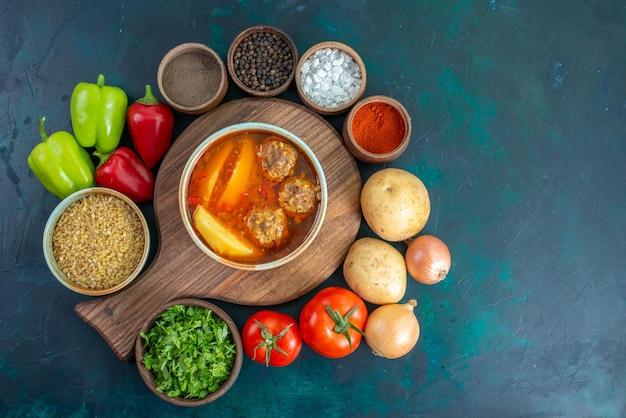 Vista superior da sopa de almôndegas com batatas fatiadas no interior e legumes frescos em uma superfície azul-escura