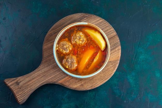 Vista superior da sopa de bolinhos de carne com batatas em círculo na superfície azul escura