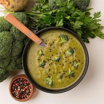 Vista superior da sopa de brócolis de inverno em uma tigela com colher e aipo