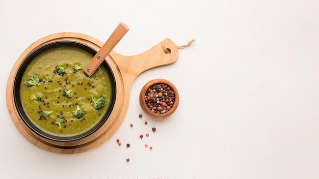 Vista superior da sopa de brócolis de inverno em uma tigela com uma colher e copie o espaço