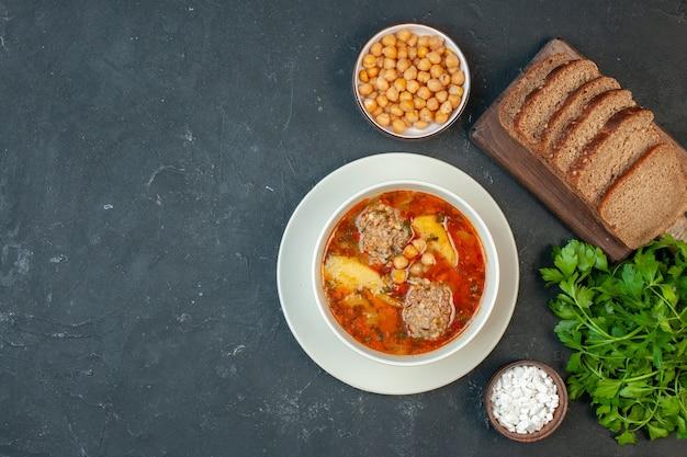 Vista superior da sopa de carne com pães em um fundo cinza escuro