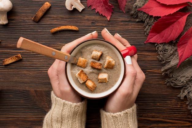 Vista superior da sopa de cogumelos de inverno em uma caneca segurada pelas mãos com croutons e colher