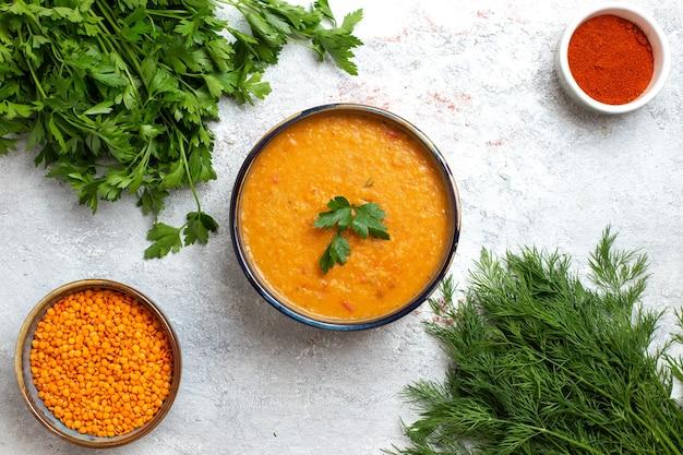 Vista superior da sopa de feijão chamada merci dentro de um pratinho com verduras na superfície branca refeição de sopa comida feijão vegetal