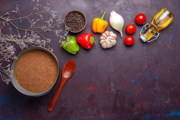Vista superior da sopa de feijão com azeite e vegetais em fundo escuro.