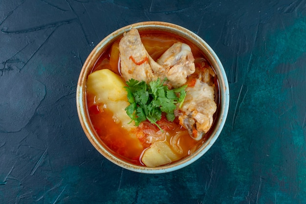 Vista superior da sopa de frango com frango e verduras dentro de uma mesa azul-escura sopa comida carne jantar frango