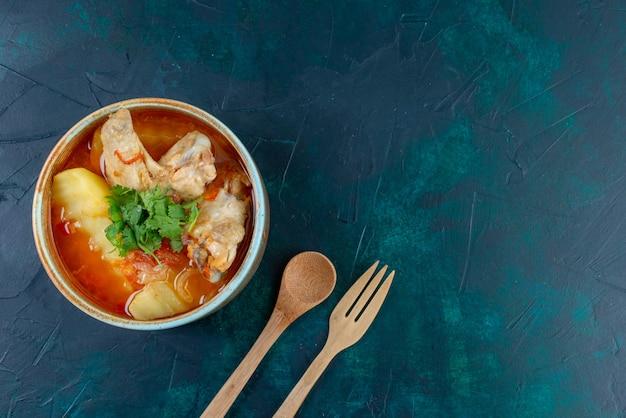 Vista superior da sopa de galinha com frango e verduras dentro, juntamente com talheres de madeira na mesa azul-escura sopa carne comida frango