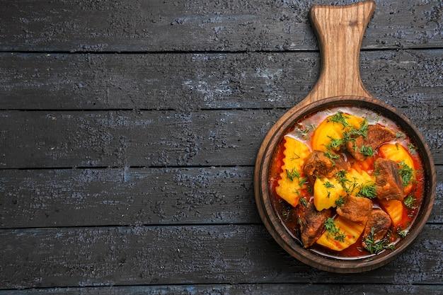 Vista superior da sopa de molho de carne com batatas e verduras na mesa escura