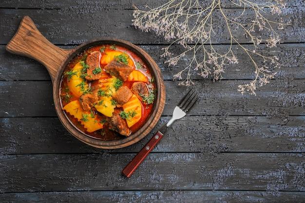 Vista superior da sopa de molho de carne com verduras e batatas na mesa escura